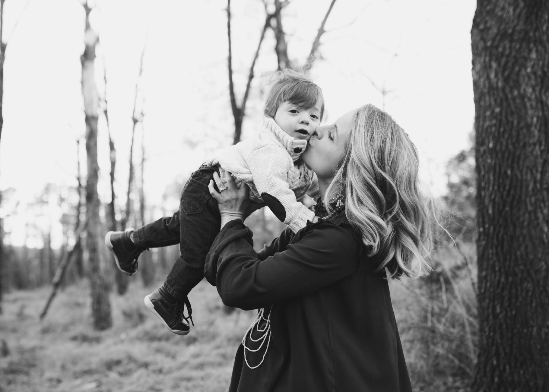 grayscale photo of woman kissing toddler on cheek standing beside tree